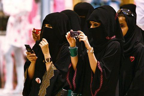 donne con velo islamico e cellulare