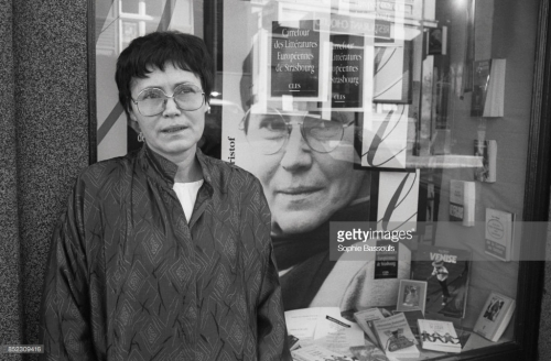 Agota Kristof (1935-) stands outside the window of a bookstore displaying her works. She is in Strasbourg to attend the Crossroads of European Literature event in October 1989.